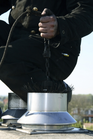Man Feeding A Sweeping Brush Into A Chimney