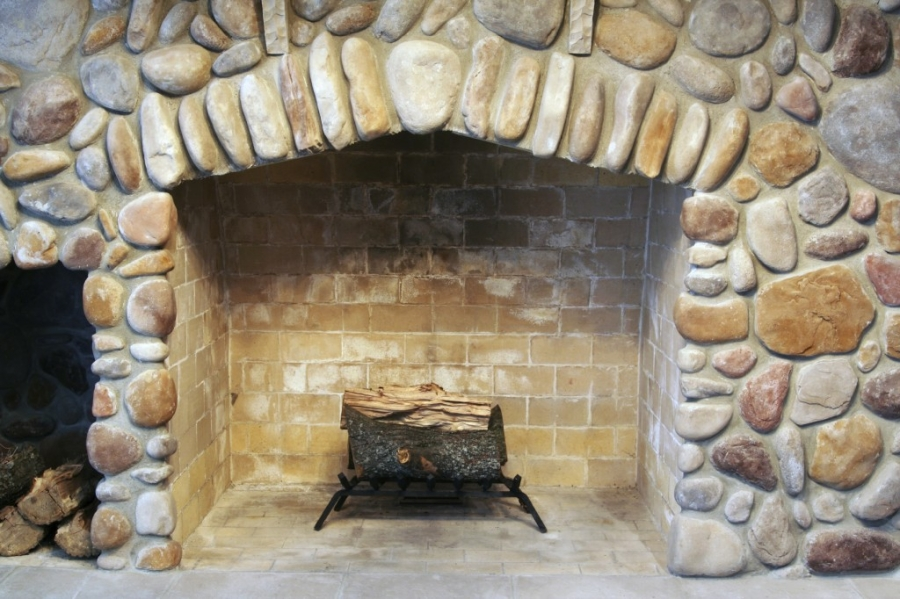 Rustic style mansonry fireplace with simply 2 logs on a stand, typically found in older homes.